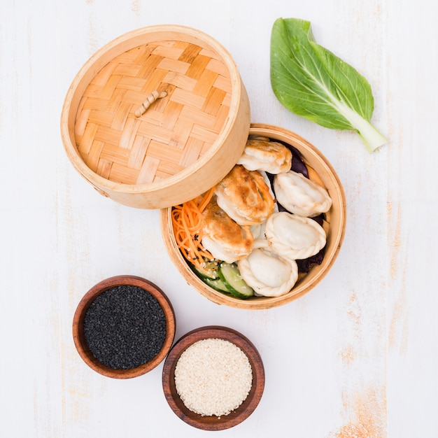 An open bamboo steamers with dumplings and sesame seeds on textured backdrop Free Photo