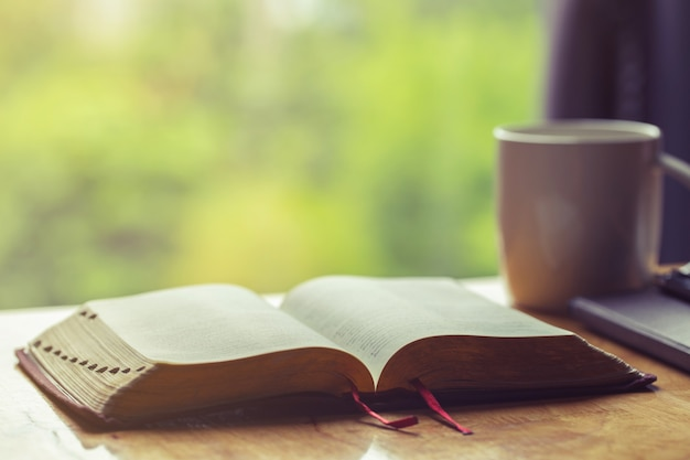 Open bible with a cup of coffee for morning devotion on wooden table with window light Premium Photo