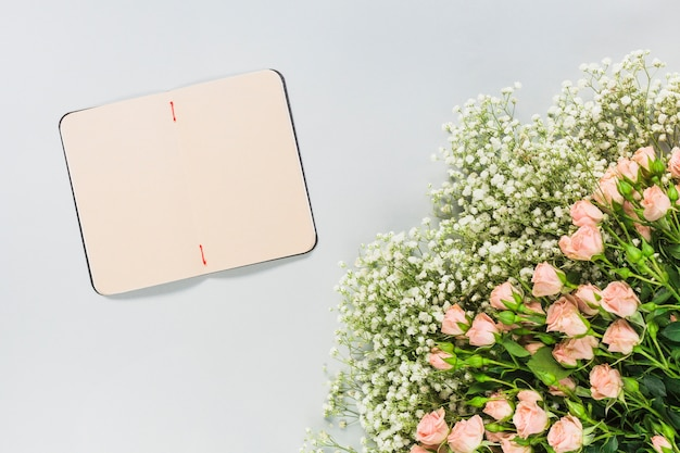 An open blank diary with flower bouquet on white background Free Photo