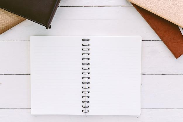 나무 테이블에 빈 흰색 페이지와 빈 메모장을 엽니 다 프리미엄 사진