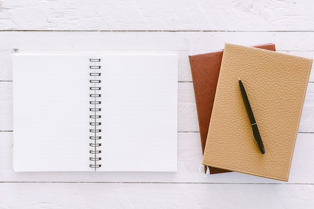 Open blank notepad with empty white pages on wooden table Premium Photo