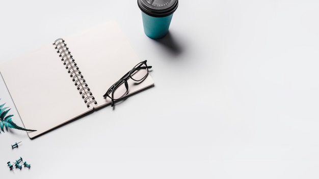 An open blank spiral notebook with eyeglasses; disposable coffee cup and push pins on white background Free Photo