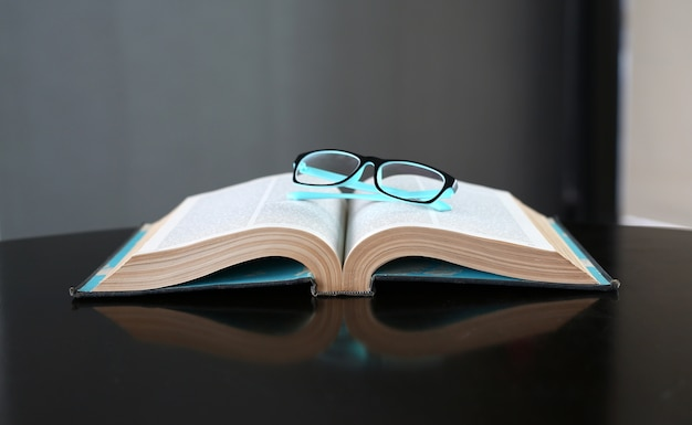 Open book, hardcover books and glasses on wooden table. education background. Premium Photo