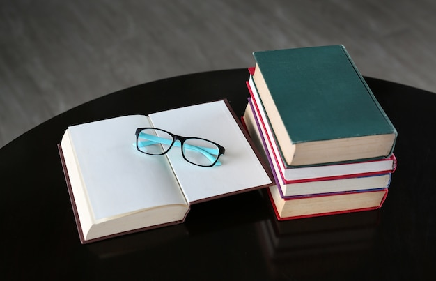 Open book, hardcover books and glasses on wooden table Premium Photo