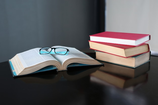 Open book and hardcover books on wooden table in library. Premium Photo