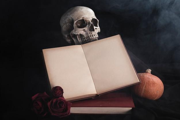 バラと頭蓋骨の開いた本のモックアップ 無料写真