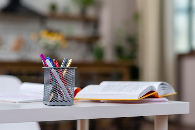 Open book and pens on the table Free Photo
