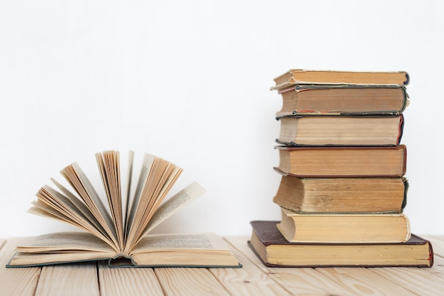 An open book next to a stack of vintage books on a wooden surface against a white wall. Premium Photo