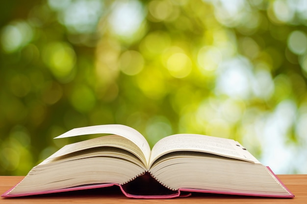 Open book on table in front of green bokeh background Premium Photo
