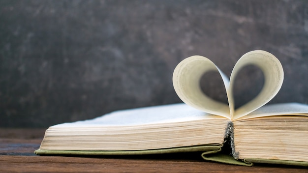 Open book with heart shape from paper page on dark wood table Premium Photo
