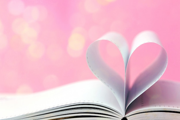 Open book with heart shape on light bokeh pink background. valentine's day concept. minimal style. Premium Photo
