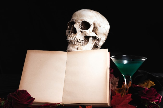 Open book with human skull and drink Free Photo