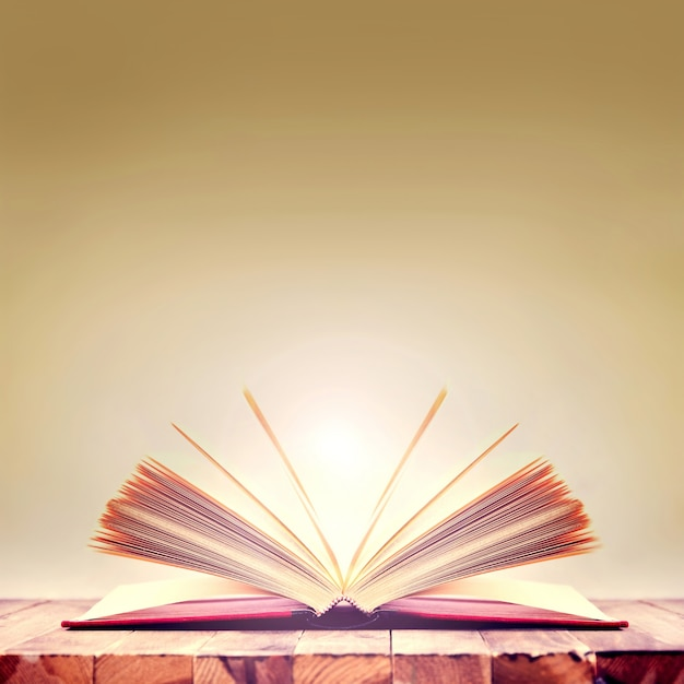 Open book on wooden table. Free Photo
