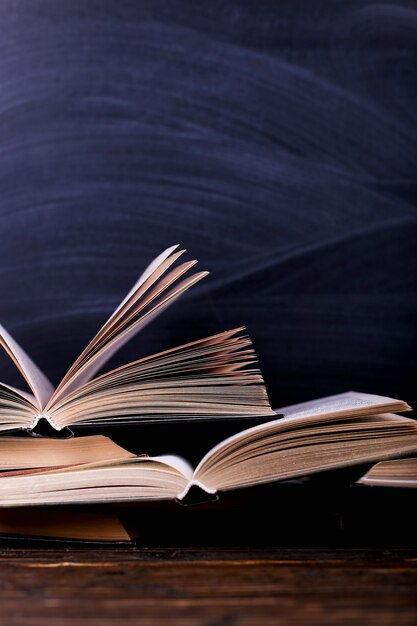 Open books are a stack on the desk, against the background of a chalk board Premium Photo
