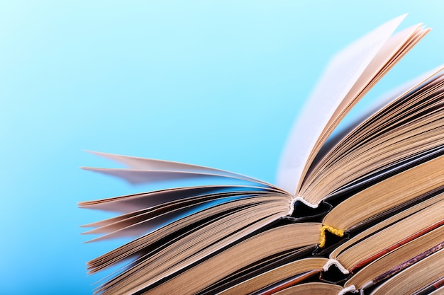 Open books are stacked on the desk on blue. difficult homework at school, a mountain of knowledge. Premium Photo