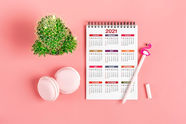 Open calendar january 2021, candles, pen, sweets, succulents on pink table Premium Photo