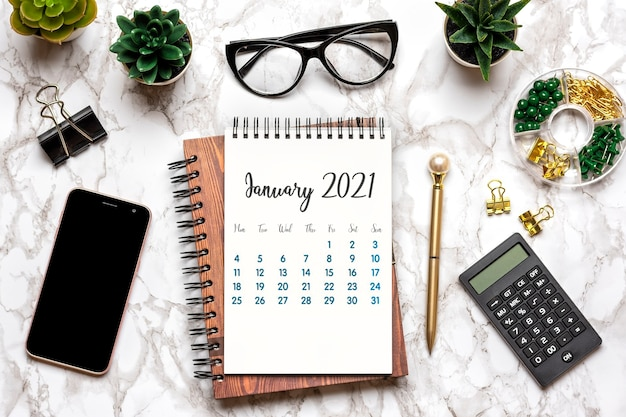 Open calendar january 2021, glasses, cup of coffee, pen, smartphone, succulents on marble table Premium Photo