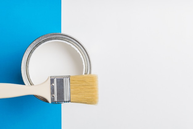 An open can of white paint and a brush on a blue and white Premium Photo