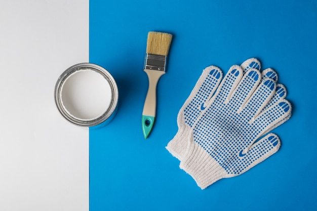 An open can of white paint, gloves and a brush on a blue and white Premium Photo