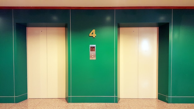 Open and closed chrome metal office building elevator doors realistic photo. Premium Photo