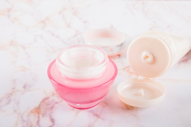 Open container of moisturizing cream on marble Free Photo