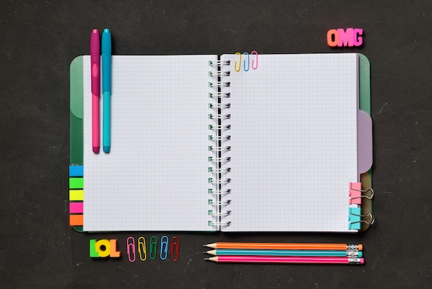 Open copy book with office and student supplies on black chalk Premium Photo