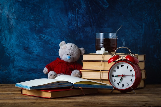 Open diary; cup of tea; books; toy bear; red alarm clock on blue surface. school concept Premium Photo