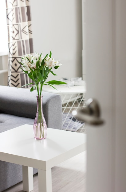 Open door to room with bouquet of flowers on table, scandinavian interior Premium Photo