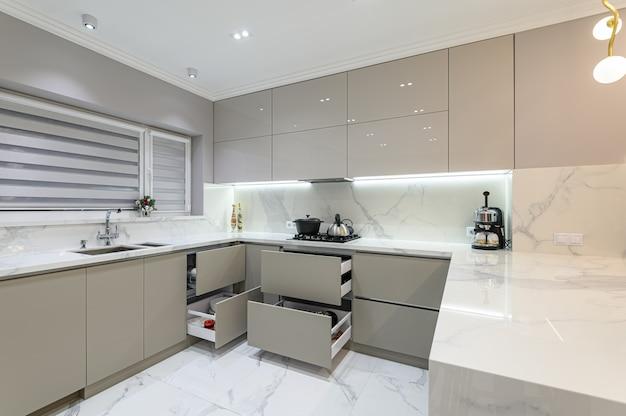 Открытые ящики на современной белой кухонной мебели Premium Фотографии