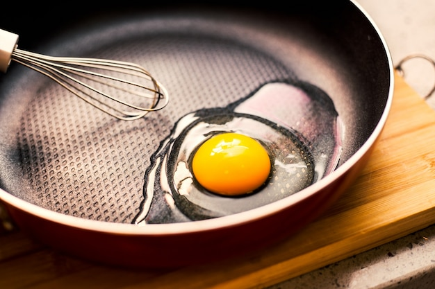 Open egg in a frying pan Free Photo