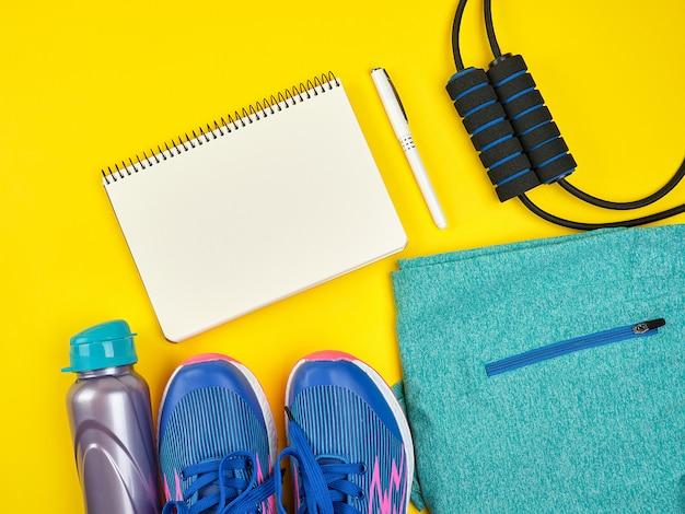 Open empty notebook and sports women's clothing for sports and fitness Premium Photo
