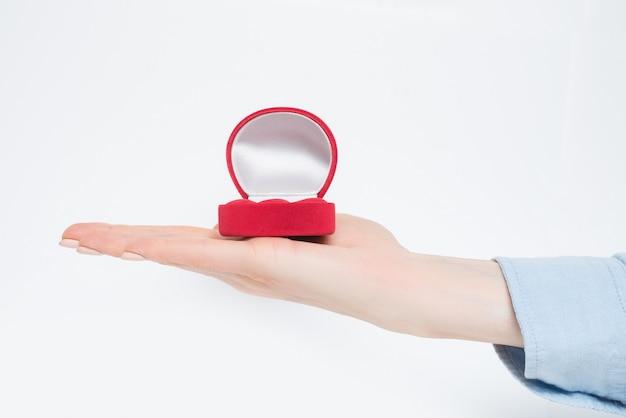 Open empty red jewelry box on female hand. Premium Photo