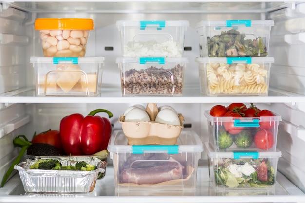 プラスチック製の食品容器と野菜を備えたオープン冷蔵庫 無料写真
