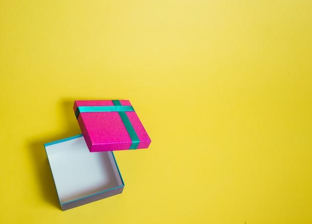 黄色のスペースにギフトボックスを開きます。ターコイズブルーのリボンとピンクのギフトボックス。サマーセール。 Premium写真