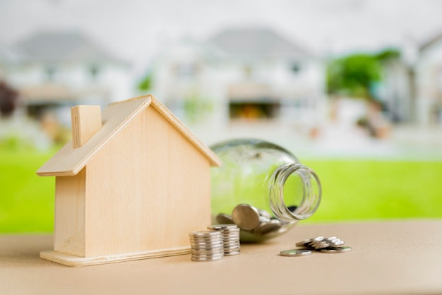 An open glass bottle; coins near the wooden house model on table at outdoors Free Photo