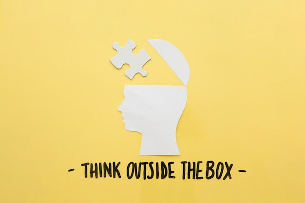 Open human brain with jigsaw piece near think outside the box message Free Photo