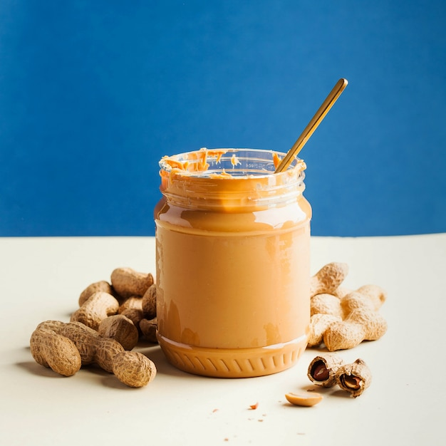 An open jar of peanut butter with a spoon and peanuts in the shell around on a colored wall. quick breakfast, food for vegetarians. Premium Photo