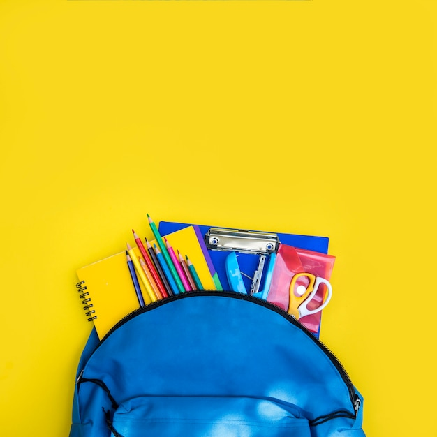 Open knapsack with set of stationery Free Photo