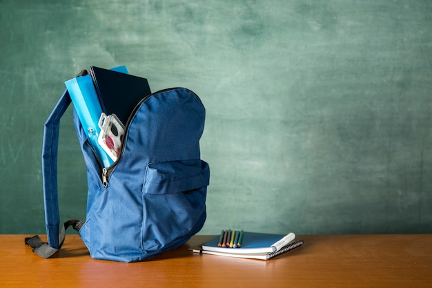 Open knapsack with stationery and watercolors Free Photo