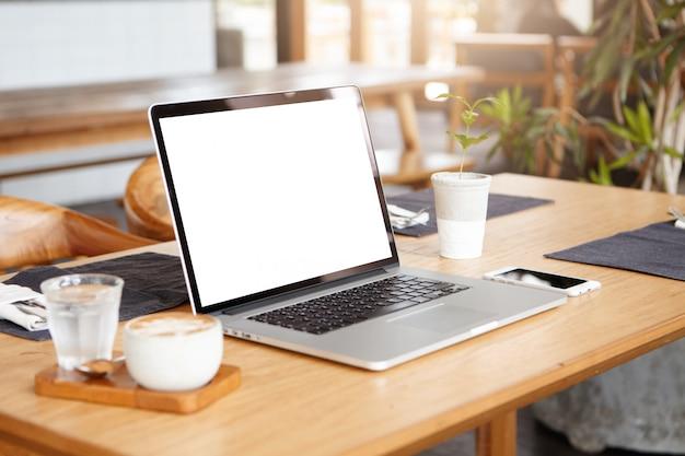 Открытый ноутбук с пустым белым экраном на столе Бесплатные Фотографии