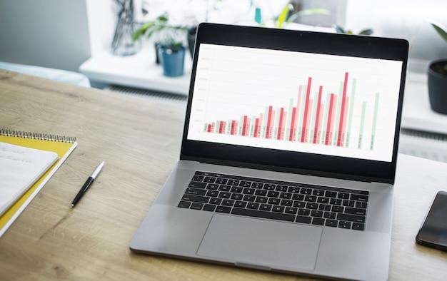 홈 오피스의 테이블에 비즈니스 차트가있는 오픈 노트북 프리미엄 사진