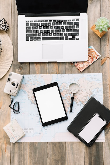 An open laptop with camera; digital tablet; magnifying glass; diary and cell phone on map Free Photo