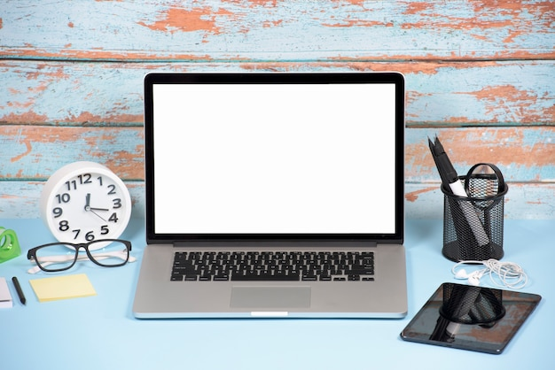 An open laptop with white blank screen; digital tablet and stationeries on blue desk Free Photo