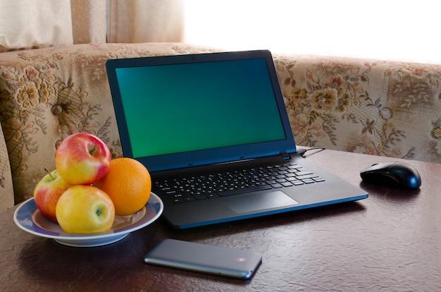 노트북, 과일 접시, 아늑한 주방의 테이블에 스마트 폰을 엽니 다. 단절 프리미엄 사진