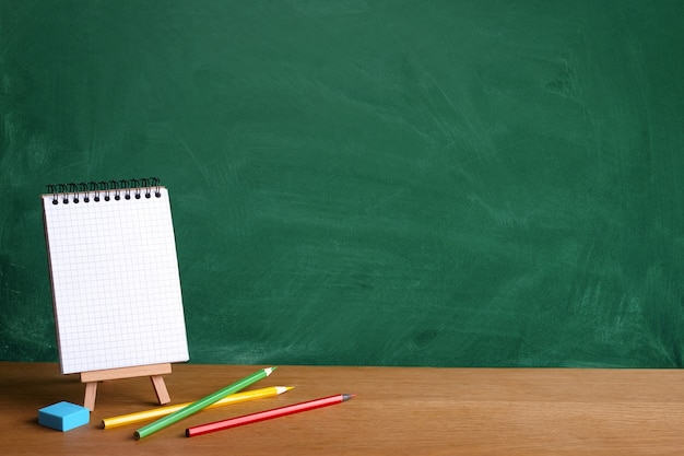 Open notebook on miniature easel and colored pencils on the background of a green chalkboard with chalk stains, copy space Premium Photo