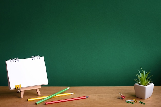 Open notebook on miniature easel, succulent in a pot and colored pencils on the background of a green chalkboard, copy space Premium Photo
