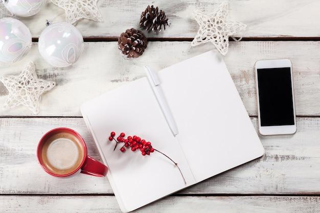 電話とクリスマスの装飾が施された木製のテーブルでノートブックを開く 無料写真