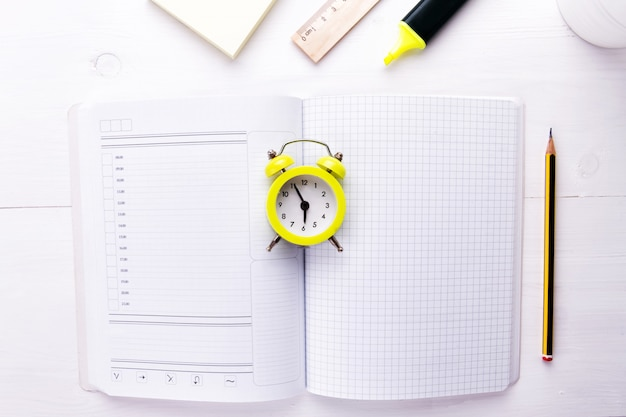 An open notebook with an alarm clock and office supplies Premium Photo