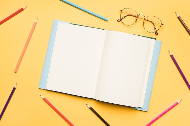 Open notebook with blank pages surrounded by pencils Free Photo