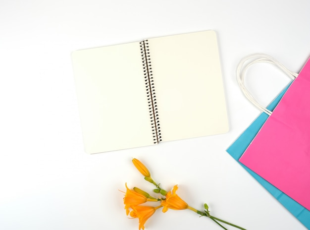 Open notebook with blank white sheets and multi-colored paper shopping bags Premium Photo